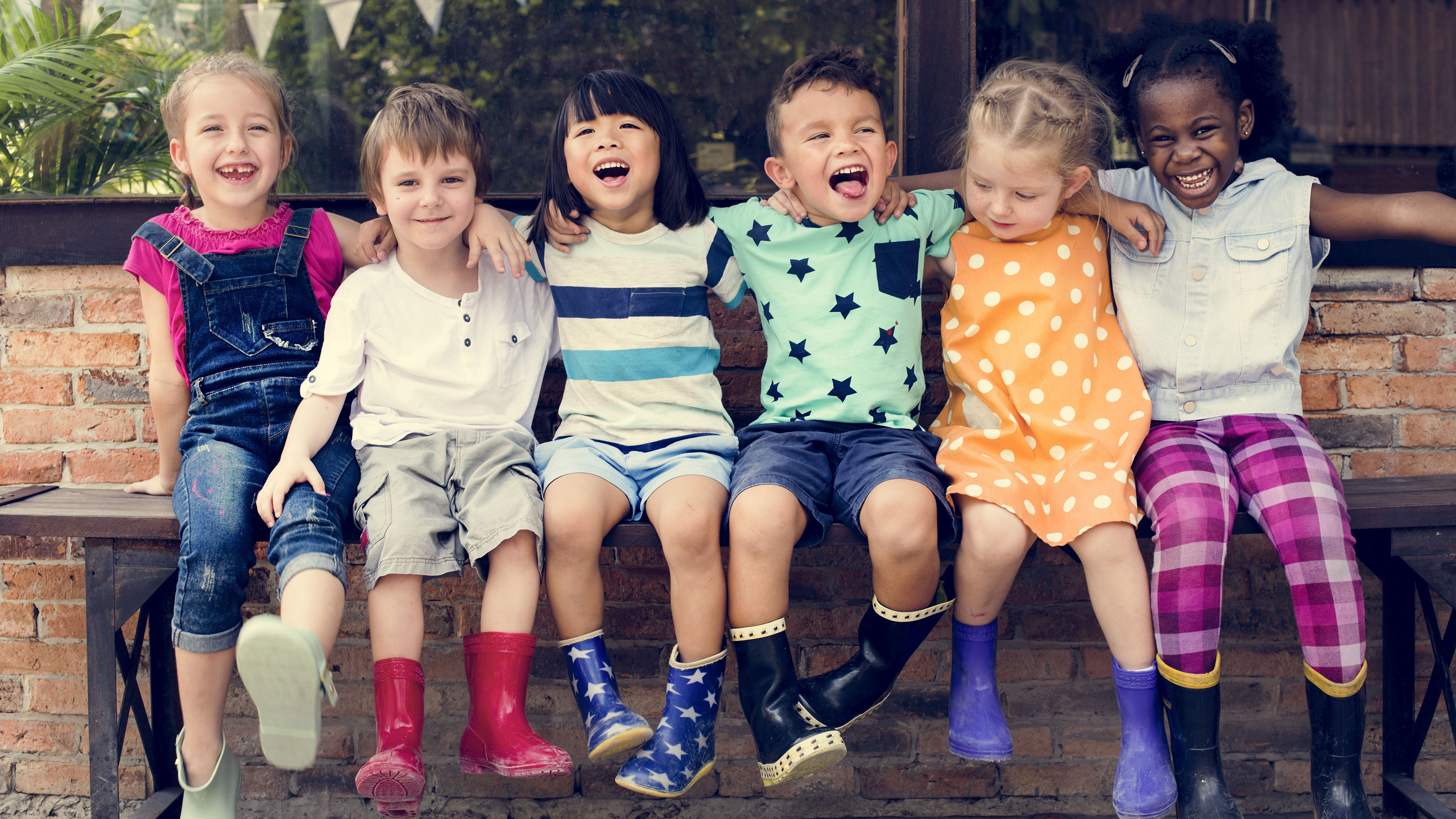 Image of six laughing children with colorful rain boots
