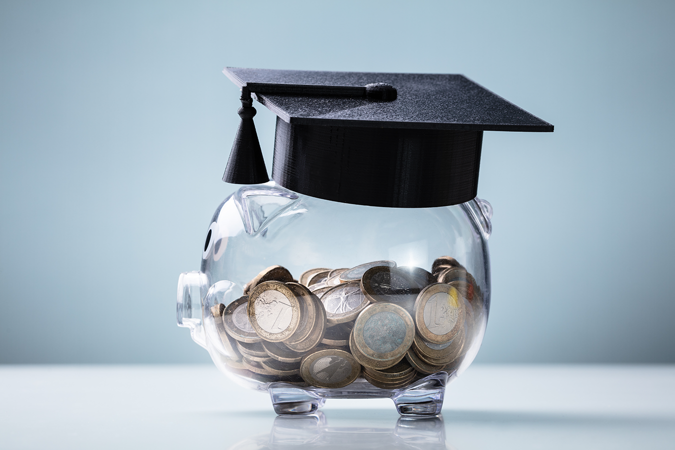 Image of Black Graduation Hat on top of a clear piggybank with coins visible inside