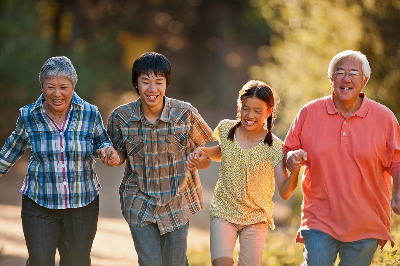 A multi-generational Asian family holds hands while walking in nature