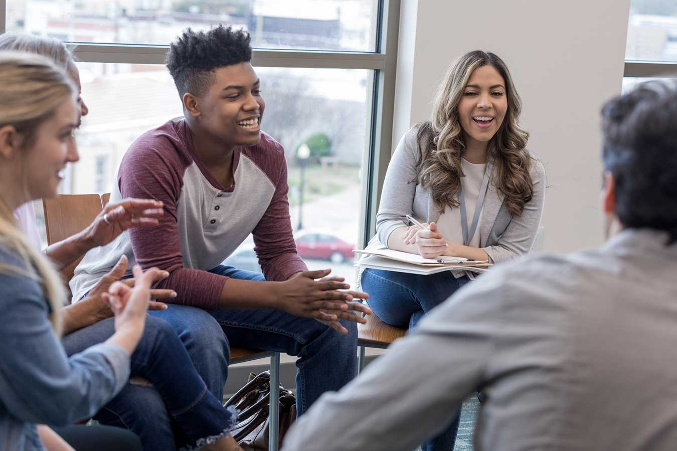 Image of diverse group of young adults sitting on chairs in a circle discussing, laughing