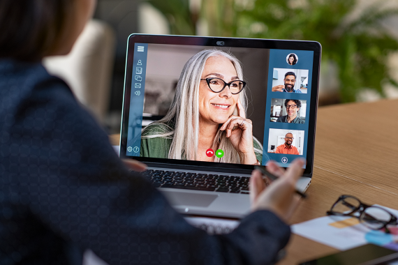 Image of a person looking at a laptop with 5 people on video conference