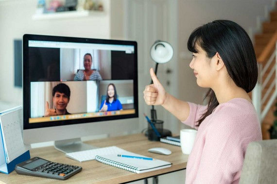 Image of an Asian woman working from home giving a thumbs up sign to videoconference colleagues visible on her laptop