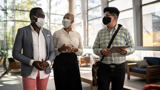 Three co-workers walking in an office lobby with their COVID-19 masks on