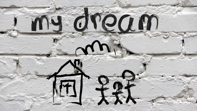 """Kids sketch of house with stick figure family and the words """"my dream"""" above it on background of painted white bricks"""