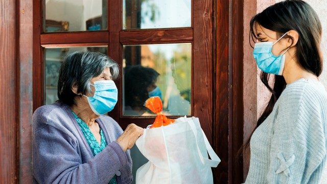 Teenage girl volunteer delivering groceries to a senior woman during the COVID 19 pandemic