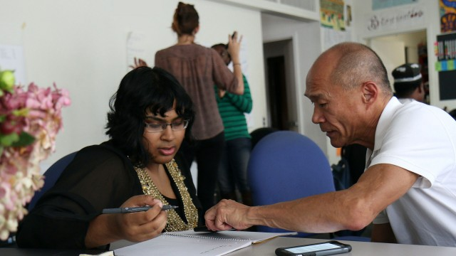 Multiple sets of two people collaborating in a work room, different ages, races, sizes of people