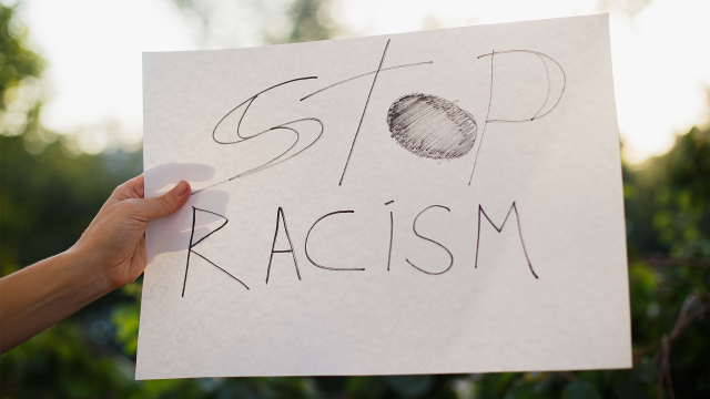 "Woman holding white paper with text ""Stop racism"". Against the background of trees and sunlight"