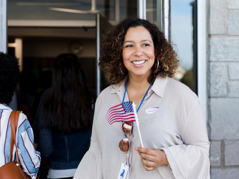 """Lady holding an an American flag with an """"I voted"""" sticker"""