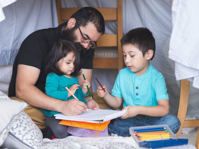 Image of Native American dad drawing with his young daughter and son in living room camp