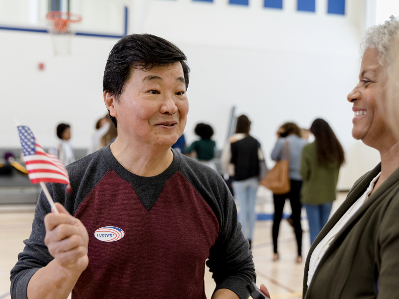 Man with an American flag talking to women at a voting center