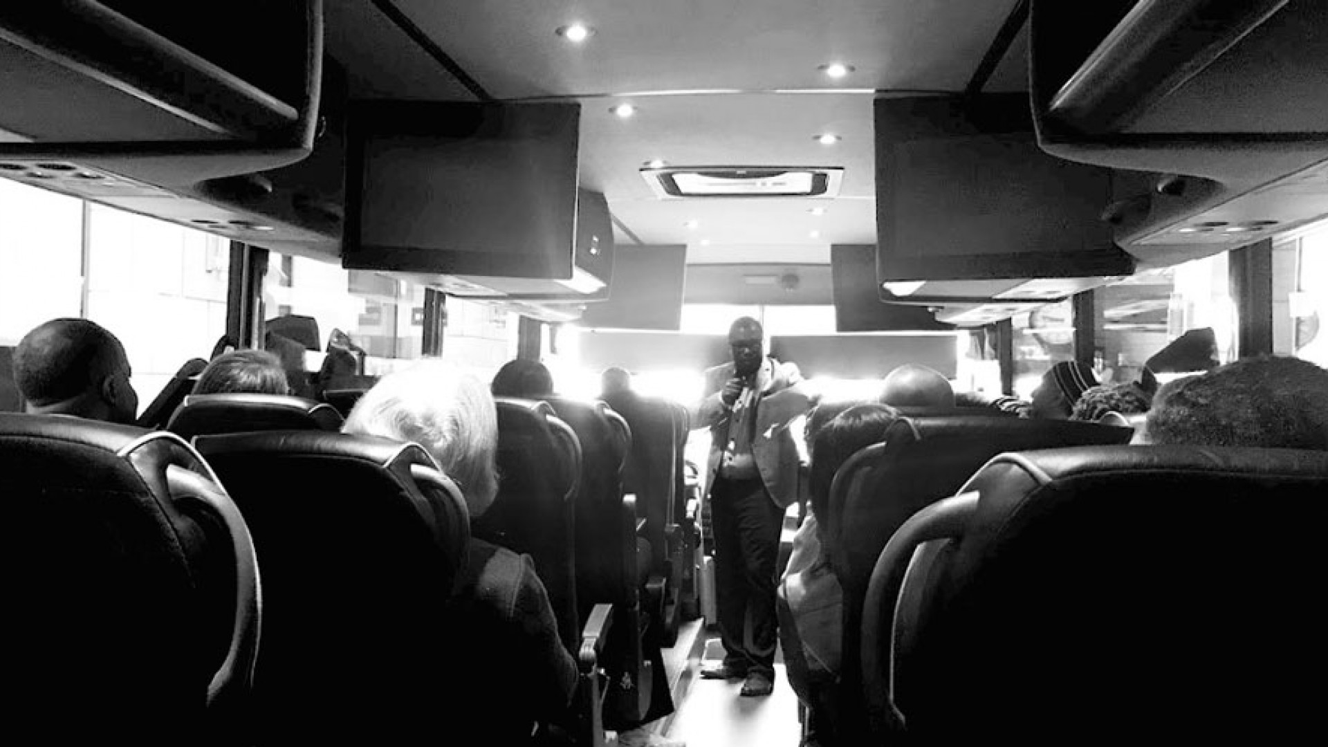 Black and white picture of Boukman Mangones speaking to people sittin on a bus