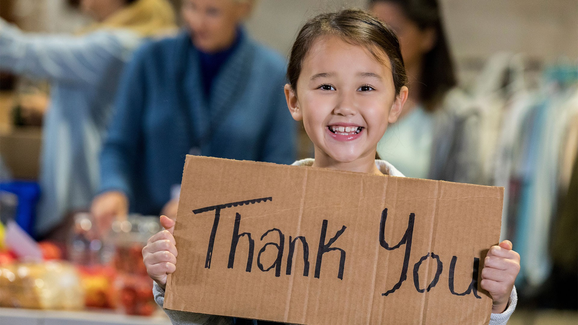 Little girl with thank you sign in a food bank
