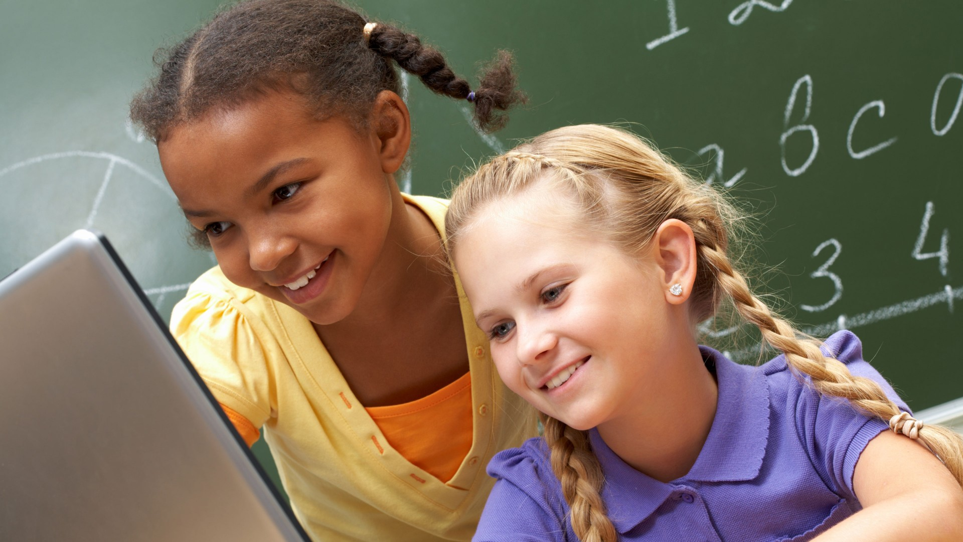 Two smiling school-age girls, one black, one white, loot at a laptop with a blackboard in the background