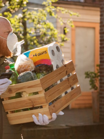 Man in a mask delivering food and groceries