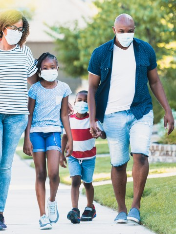 Family wear face masks while walking in their neighborhood during the COVID-19 pandemic.