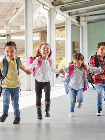 Elementary school students running through a hallway