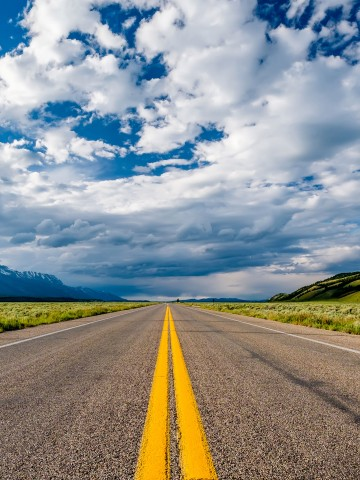Picture of an open empty highway with green grassland on the side and mountains and hills in the distance