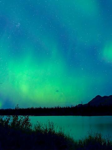 Image of Aurora Borealis green lights against blue sky over a lake in Denali National Park, Alaska