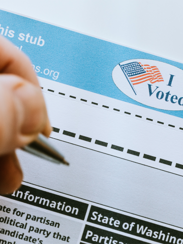 A close up of a persons hand filling in votes on a voters ballot to be mailed in.