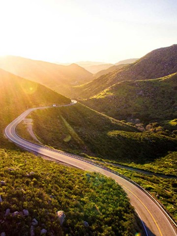 Picture of sunshine breaking over hills into a rural valley with a two lane winding road