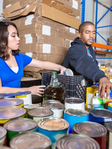Two people sorting canned goods at a food bank